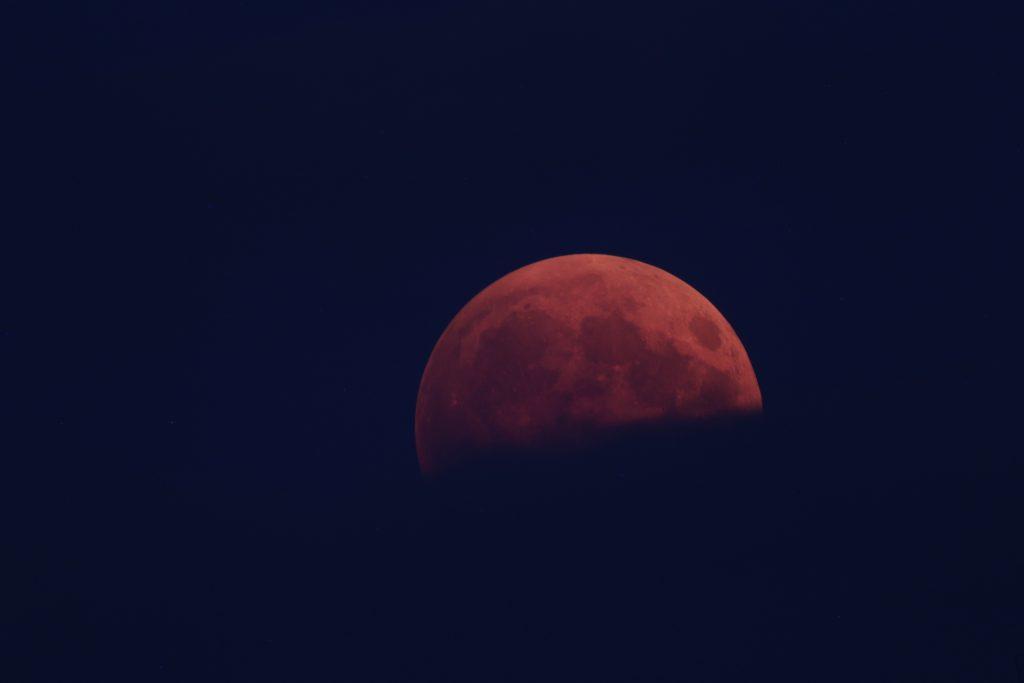 Der Mond steigt über das Wolkenband